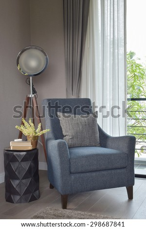 Light Blue Armchair With Gray Pillow And Retro Lamp In The Living Room