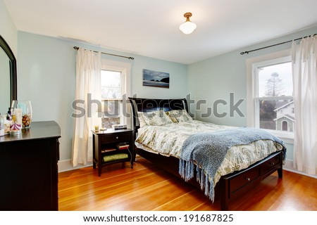 Light blue bedroom with two windows and hardwood floor. Furnished with black furniture set