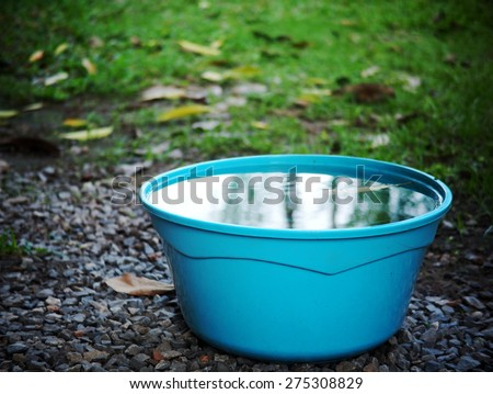light blue color plastic water bucket on garden floor outdoor surrounding with green area environment and blue sky reflections on the water surface in the bucket - stock photo