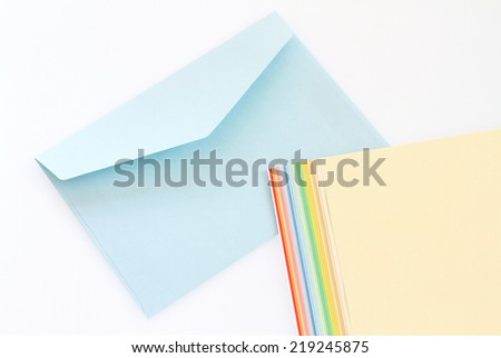 Light blue envelope and notepaper on white background - stock photo