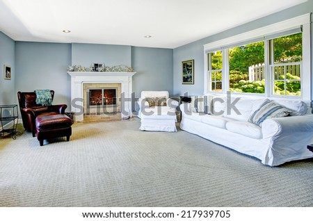 Light blue living room with white sofa, armchair and leather chair and cozy fireplace - stock photo