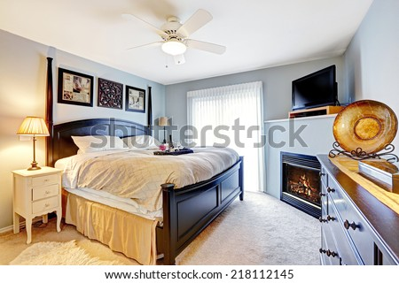 Light blue master bedroom with queen size bed, dresser. Room has fireplace and TV - stock photo