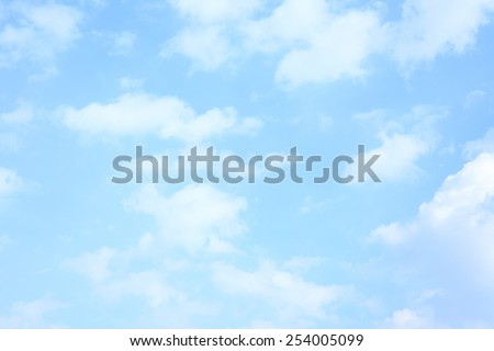 Light blue spring sky with clouds, may be used as background - stock photo