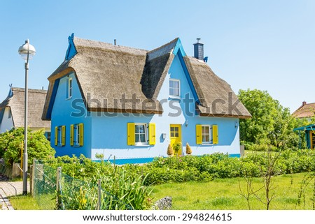 light-blue thatched-roof house with garden - stock photo