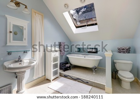 Light blue velux bathroom with window. View of white antique freestanding bath tub, washbasin stand and toilet - stock photo