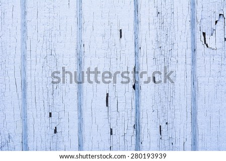 Light blue wooden wall with worn, cracked paint due to the influences of weather and age - stock photo