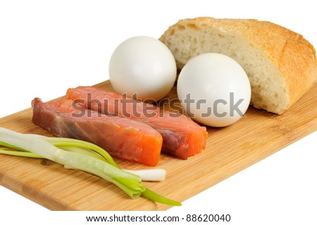Light breakfast. Eggs, salted salmon, muffin and onion on a wooden board. Isolated on white.
