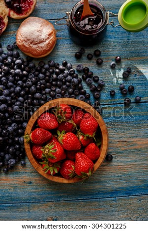 Light breakfast for the whole family, fresh blueberries and strawberries and muffin marmalade of currant - stock photo