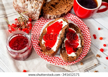 light breakfast or lunch , sandwiches of rye bread with butter , raspberry jam , berries and black tea on the background of the village