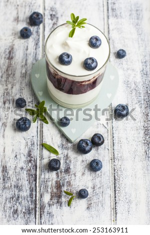 Light breakfast setup with yogurt on white wooden table. Plane Greek style yogurt with jam and loose blueberries on heart shaped coaster over white painted grunge style wooden table. - stock photo