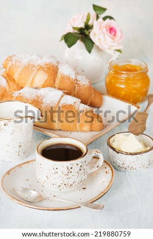 Light breakfast with a cup of coffee, croissants, orange jam and butter - stock photo