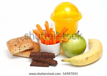 Light breakfast with green apple, banana, juice, chocolate, yoghurt, corn bread and fresh carrots on white background - stock photo