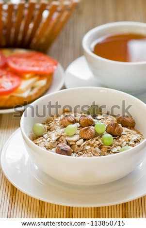 light breakfast with tea, fruit, sandwich and porridge