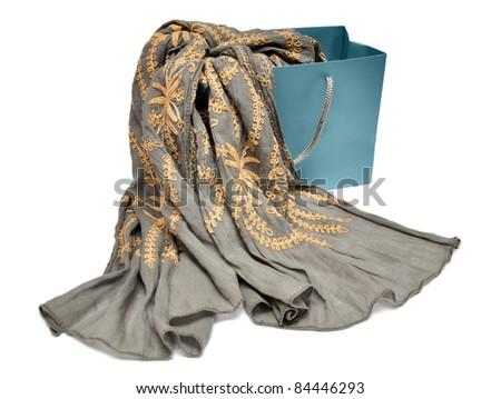 light brown scarf with golden pattern in shopping bag isolated on a white background - stock photo