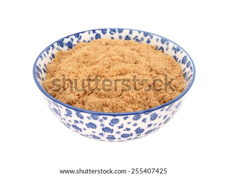 Light brown soft / muscovado sugar in a blue and white porcelain bowl with a floral design, isolated on a white background - stock photo
