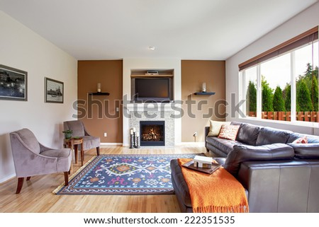 Light brown tone living room with fireplace and tv. Comfort leather couch with pillows and orange blanket - stock photo