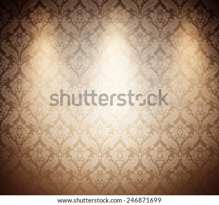 light brown wallpaper with three spots. - stock photo