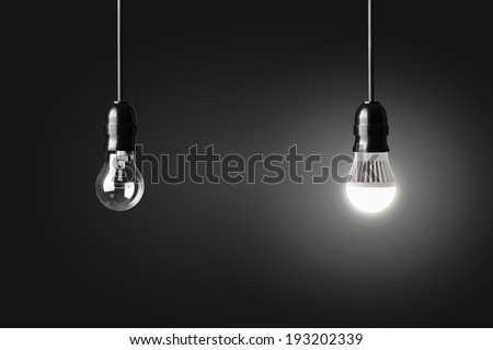 Light bulb and glowing LED bulb on black - stock photo