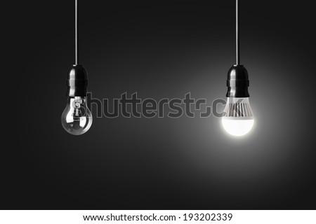Light bulb and glowing LED bulb on black - stock photo