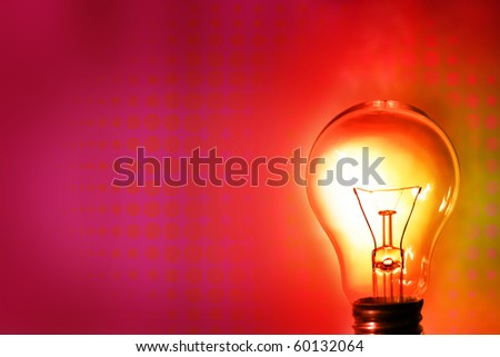 Light bulb glowing on color background