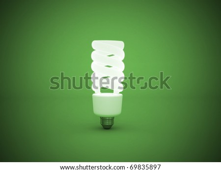 Light bulb glowing on green background - stock photo