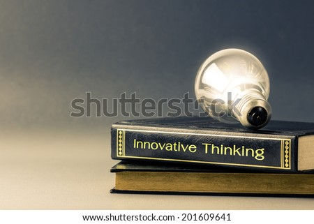 Light bulb glowing on the Innovative Thinking book - stock photo