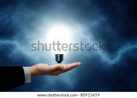 Light bulb hanging on business men. The background is a blue lightning bolt - stock photo