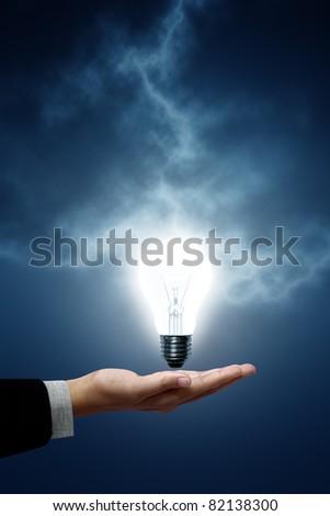 Light bulb hanging on business men. The background is a blue lightning bolt - stock photo