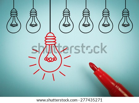 Light Bulb idea concept is on blue paper with a red marker aside. - stock photo