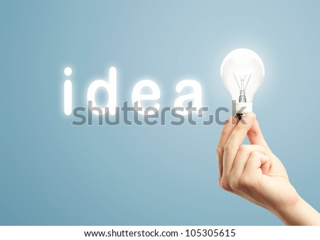 light bulb in hand and word idea on blue background - stock photo