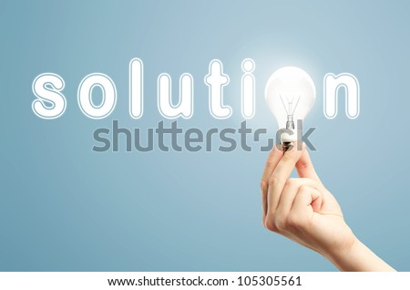 light bulb in hand and word solution on blue background - stock photo