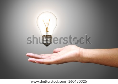 Light bulb in hand, Isolated on grey background - stock photo