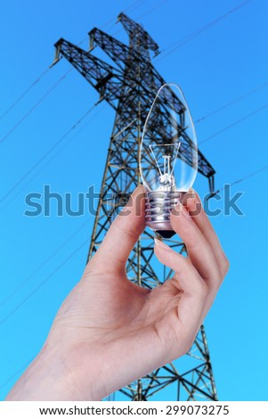 Light bulb in hand on high voltage line background - stock photo
