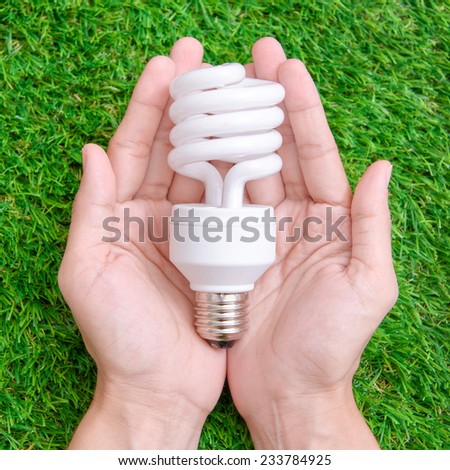Light bulb in hand with green background - stock photo
