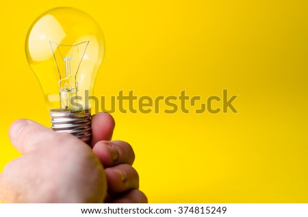light bulb in his hand on a yellow background - stock photo