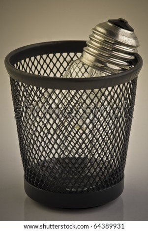 Light bulb in trash bin. Metaphor, rejected idea. Sepia.
