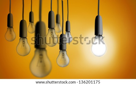 Light bulb lighting up against orange background - stock photo