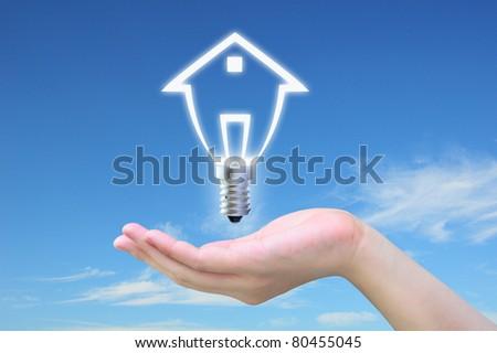 light bulb model of a house in women hand on sky - stock photo