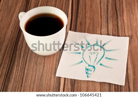 Light bulb on a napkin and cup of coffee - stock photo
