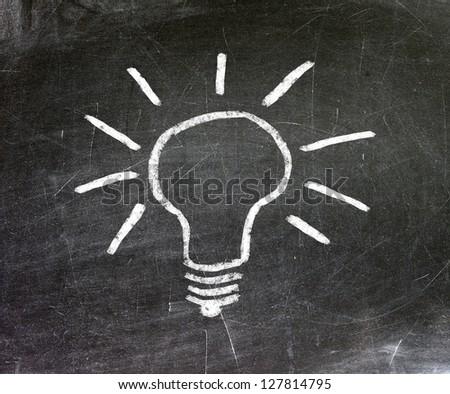 Light bulb on blackboard background - stock photo