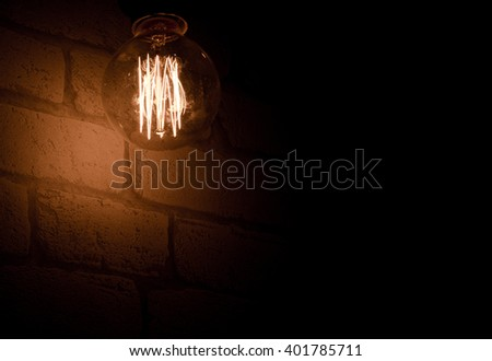 Light bulb on brick wall background switched on.