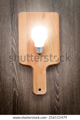 Light bulb on chopping board, serve idea concept - stock photo