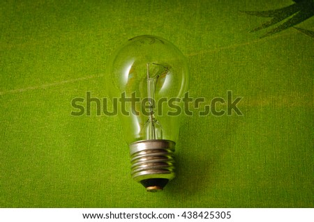 Light bulb on green background with copy space  - stock photo