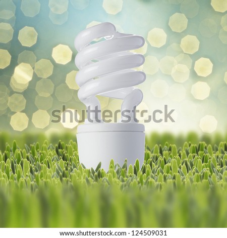 Light bulb on green grass with beautiful bokeh of lights in the background - stock photo