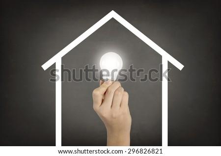 Light bulb on house shaped on blackboard - stock photo