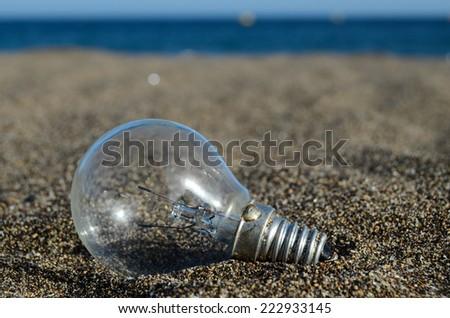 Light bulb on the beach Idea Concept - stock photo