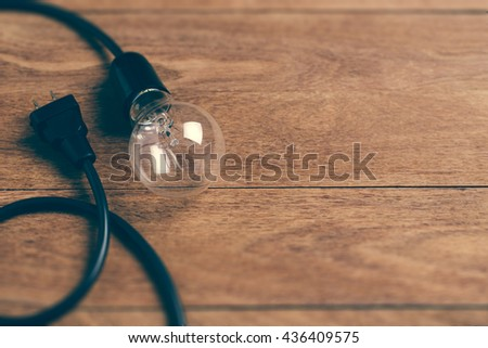 Light bulb on wooden background. Concept for save energy, idea or clever, global warming.