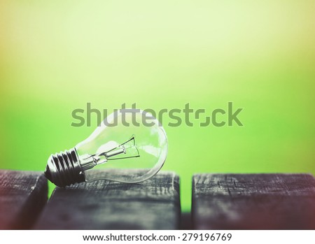 Light bulb on wooden table on nature sunny background. Environment, eco technology, energy and idea concept. - stock photo