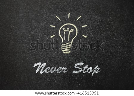 "light bulb painted on a board and the text  ""Never stop"". High sharpness"
