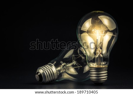 Light bulb shining in the darkness - stock photo